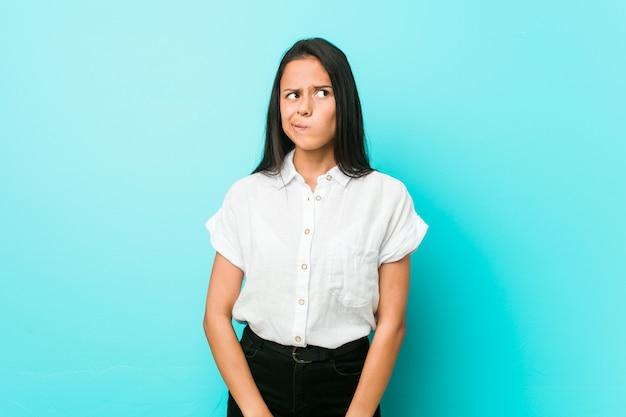 混乱している青い壁にヒスパニック系の若いクールな女性は、疑わしいと自信がありません。