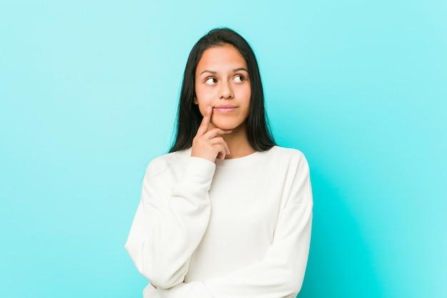 疑わしいと懐疑的な表情で横に見ている若いかなりヒスパニック系女性。