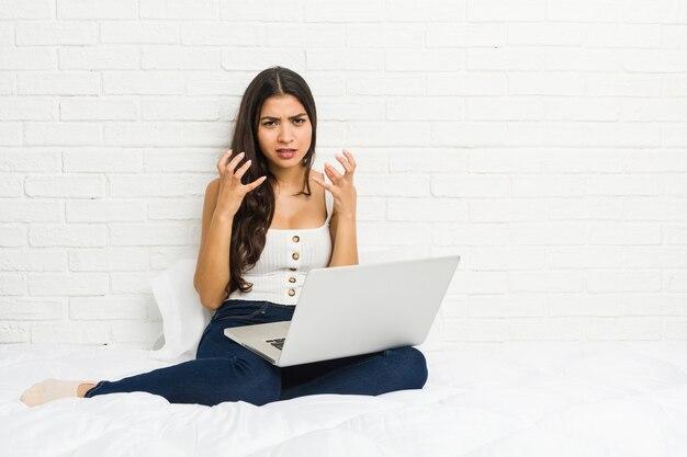 緊張した手で叫んで怒ってベッドの上の彼女のラップトップで働く若いアラブ女性。