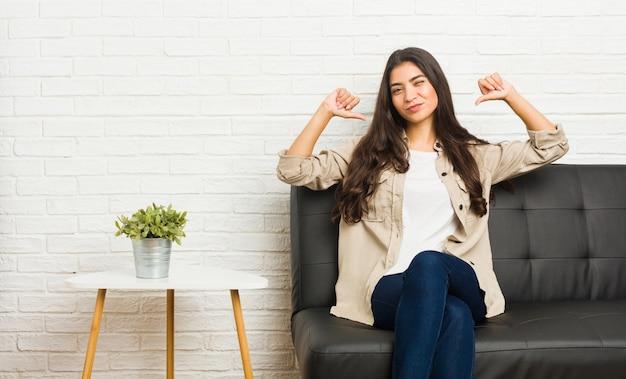 ソファに座っている若いアラブ女性は、誇りと自信を持っていると感じています。