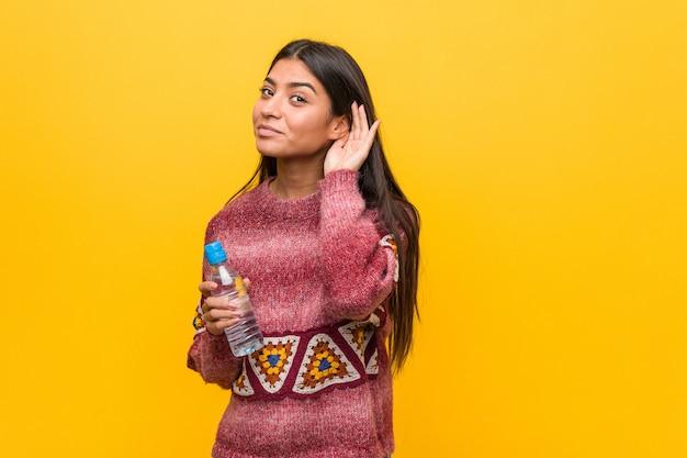 ゴシップを聴こうとして水のボトルを保持している若いアラブ女性。