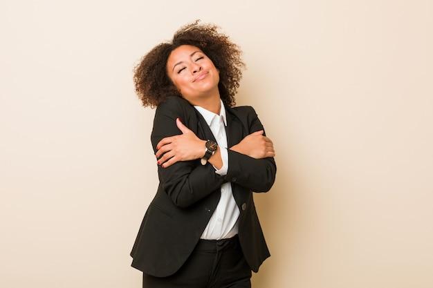 Молодой бизнес афро-американских женщина обнимает, улыбаясь беззаботной и счастливой.