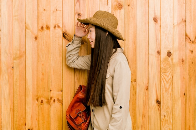 おでこに手を置いて遠くを見て若い中国人旅行者の女性。