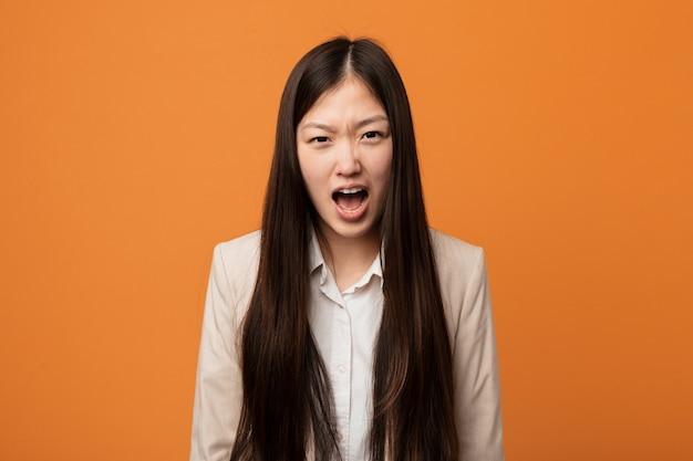 非常に怒って攻撃的な若いビジネス中国女性。