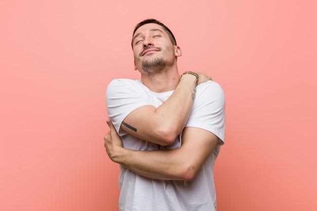 Молодой случайный человек обнимает себя, улыбаясь беззаботной и счастливой.