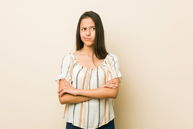 皮肉な表情でカメラで見て不幸な若いヒスパニック系女性。