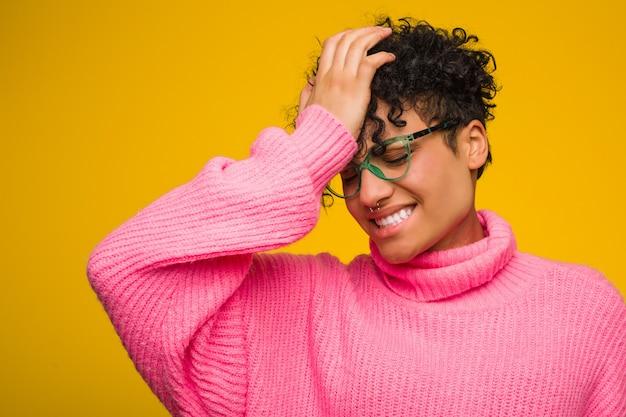 Молодая афро-американская женщина нося розовый свитер забывая что-то, шлепая лоб с ладонью и закрывая глаза.
