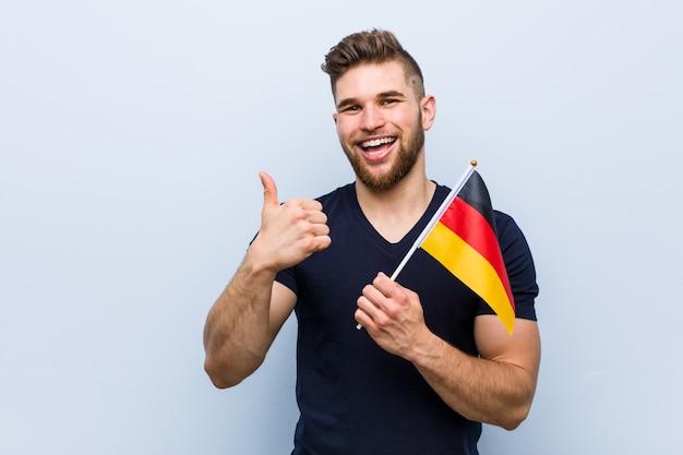 笑顔と親指を上げるドイツの旗を保持している若い白人男