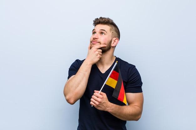 疑わしいと懐疑的な表情で横にドイツの旗を保持している若い白人男。