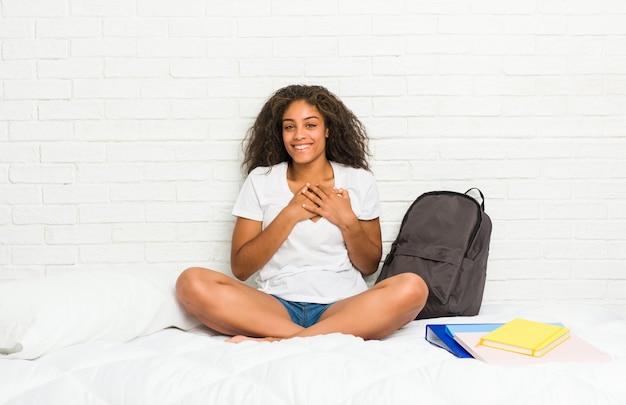 Молодой афроамериканец студент женщина на кровати имеет дружелюбное выражение, прижимая ладонь к груди. концепция любви