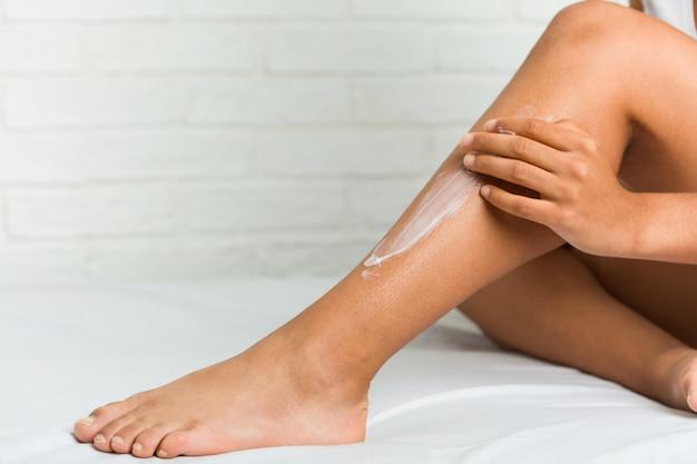 Крупным планом молодой афроамериканец женщина, получая увлажняющий крем на ее ногах