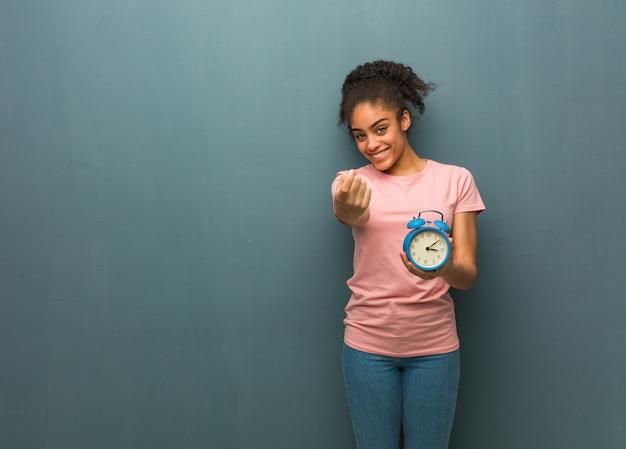 来て誘う若い黒人女性。彼女は目覚まし時計を持っています。