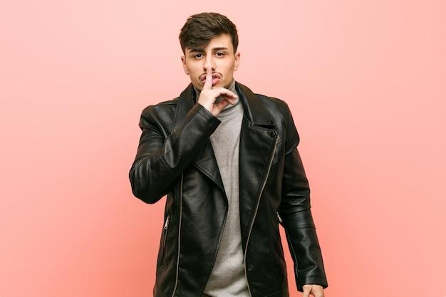 ヒスパニック系の若い男が革のジャケットを着て秘密を守ったり、沈黙を求めています。