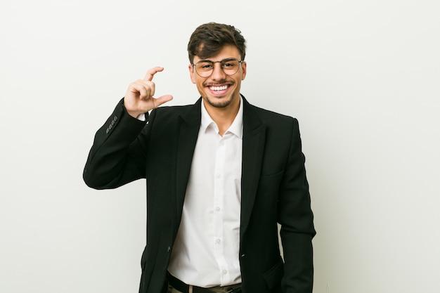 Молодой бизнес испаноязычное мужчина держит что-то мало с указательными, улыбаясь и уверенно.
