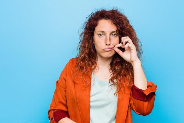 秘密を保つ唇に指で若い赤毛のエレガントな女性。