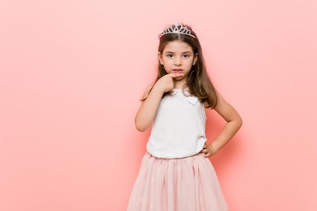 プリンセスを着た少女は、爪を噛み、神経質で非常に心配そうに見えます。