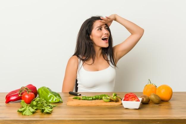 額に手を入れて遠くを見て健康的な食事を準備する若い曲線の女性。