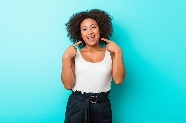 若いアフリカ系アメリカ人女性の笑顔、口に指を指しています。
