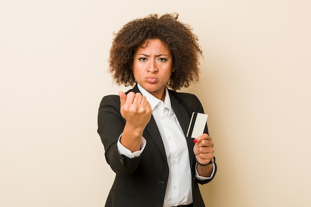 カメラ、積極的な表情に拳を示すクレジットカードを保持している若いアフリカ系アメリカ人女性。