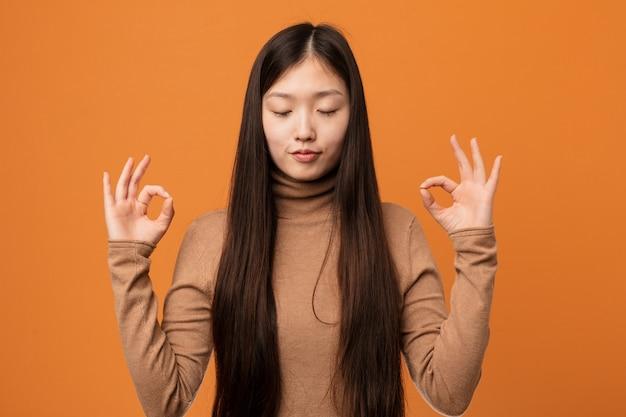 Молодая милая китаянка расслабляется после тяжелого рабочего дня, он выполняет йогу.