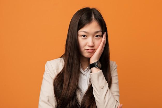 退屈して、疲れて、リラックスした日を必要とする若いビジネス中国人女性。