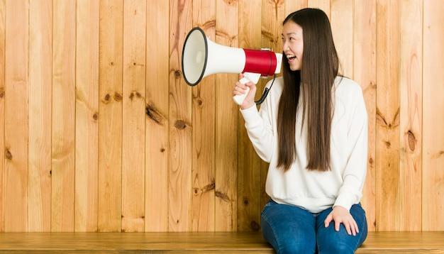 Молодая азиатская женщина сидя и говоря через мегафон