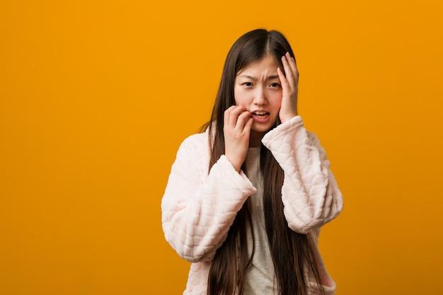 パジャマの若い中国人女性が泣き言を言って泣き叫んでいます。