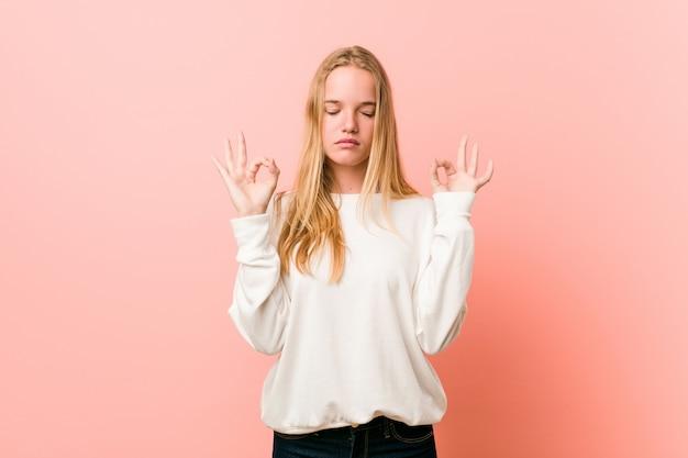 Молодая блондинка подросток женщина расслабляется после тяжелого рабочего дня, она выполняет йогу.