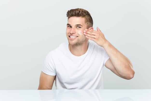 Молодой кавказский человек используя лицевой увлажнитель