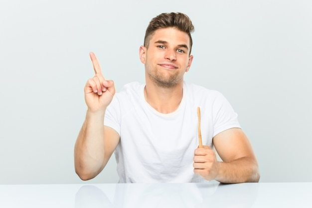 若い男が指でナンバーワンを示す歯ブラシを保持しています。