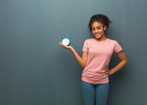 手で何かを保持している若い黒人女性。彼女は目覚まし時計を持っています。