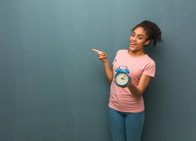 指で側を指している若い黒人女性。彼女は目覚まし時計を持っています。