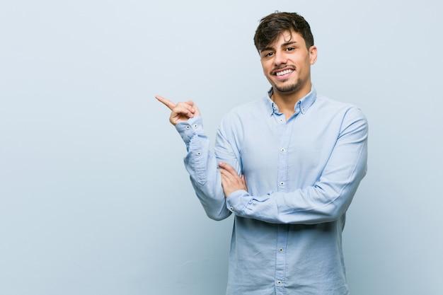 人差し指で元気に指している笑顔若いヒスパニックビジネス男。