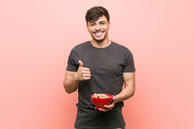 Молодой латиноамериканский человек, держащий миску каши, улыбаясь и поднимая большой палец вверх