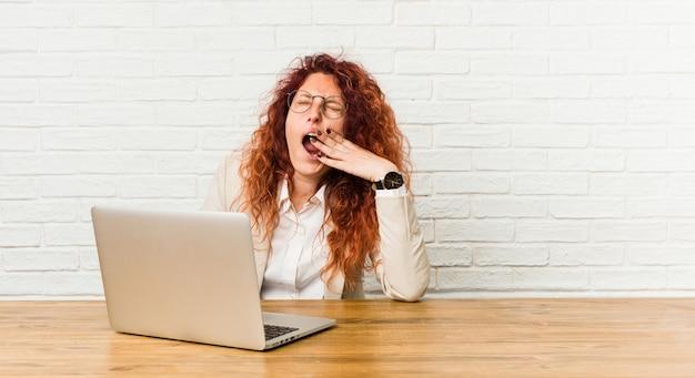 口を覆っている疲れたジェスチャーを示すあくび彼女のラップトップで働く若い赤毛の巻き毛の女性