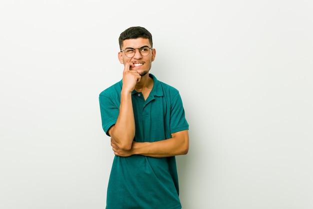 Молодой испаноязычный мужчина кусает ногти, нервничает и очень беспокоится