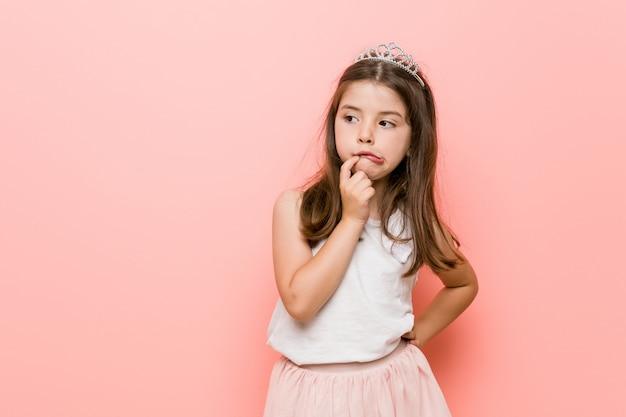 Маленькая девочка в костюме принцессы выглядела расслабленной, думая о чем-то, смотрящем на пространство копии.