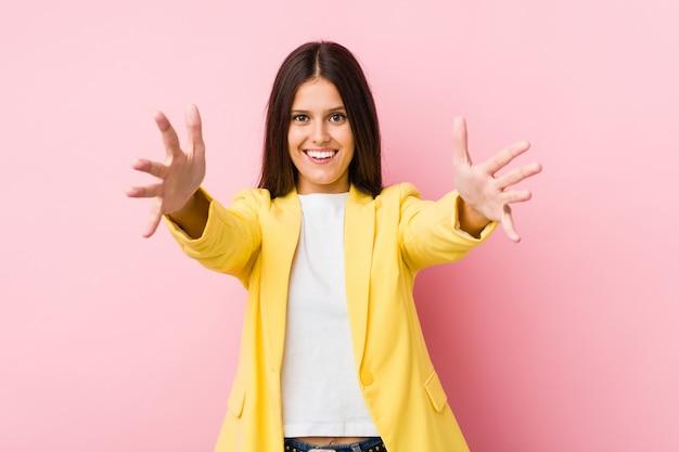 Молодой бизнес женщина чувствует себя уверенно, давая обнять камеру.
