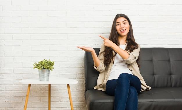 ソファの上に座っている若いアラブ女性は、手のひらにコピースペースを保持して興奮しています。