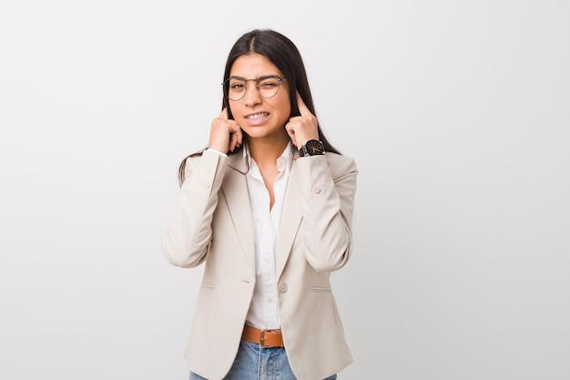 手で耳を覆う白い壁に対して隔離される若いビジネスアラブ女性。