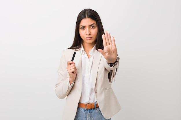 Молодая арабская женщина держа кредитную карточку стоя с протягиванной рукой показывая знак стопа, предотвращая вас.