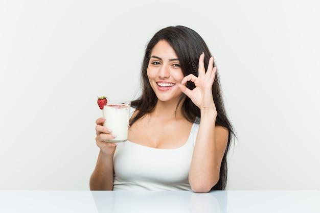 Молодая испанская женщина, держащая смузи молодая испанская женщина, держащая тост с авокадо, веселый и уверенный, показывая хорошо жест.
