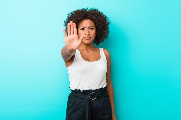 若いアフリカ系アメリカ人女性が一時停止の標識を示す差し出された手で立っているあなたを防ぎます。