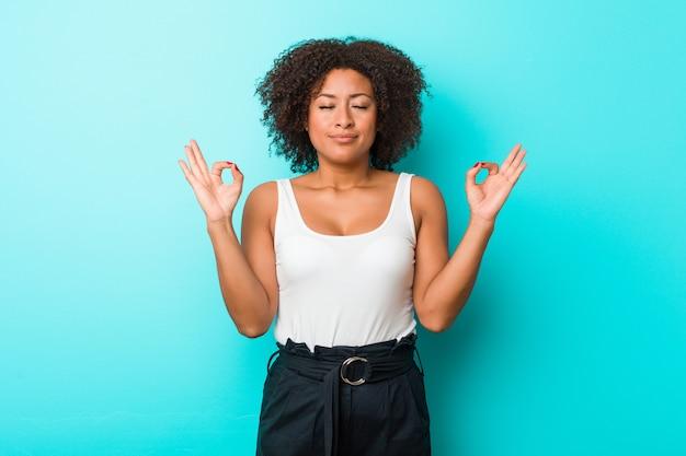 Молодая афро-американская женщина ослабляет после тяжелого рабочего дня, она выполняет йогу.
