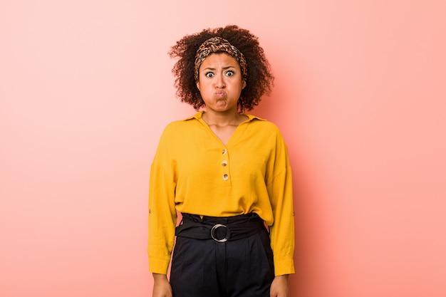 ピンクの壁に若いアフリカ系アメリカ人女性が頬を吹く、疲れた表情をしています。表情のコンセプト。