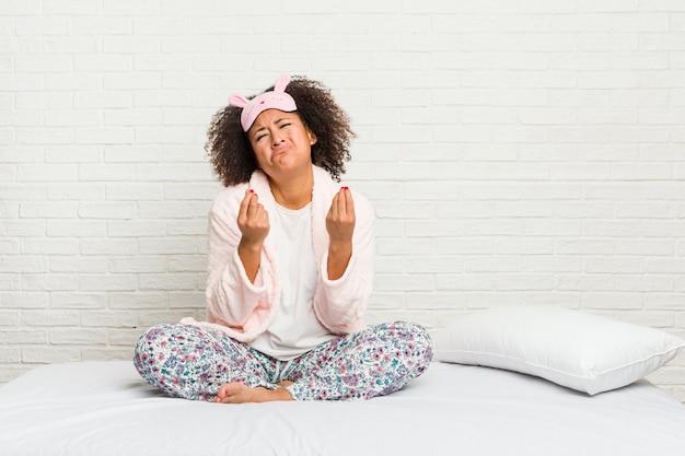 彼女はお金がないことを示すピジャマを着てベッドで若いアフリカ系アメリカ人女性。