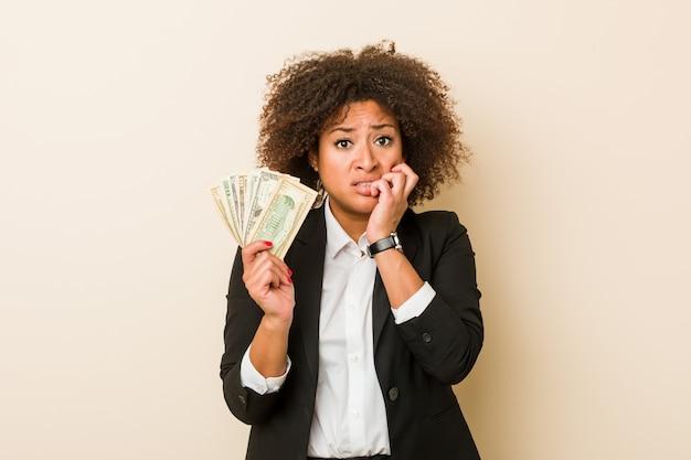 Молодая афро-американская женщина держа доллары кусая ногти, нервная и очень тревожная.