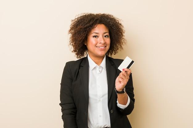 幸せ、笑顔、陽気なクレジットカードを保持している若いアフリカ系アメリカ人女性。