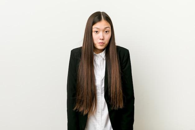 Молодая милая китайская бизнес-леди пожимает плечами плечи и смущает открытые глаза.