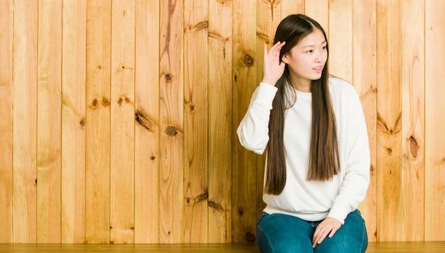 Молодая китайская женщина сидя на деревянном месте пробуя слушать сплетню.